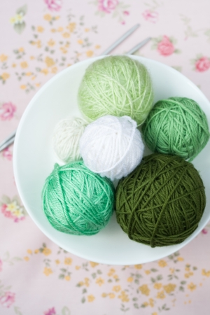 A lot of bright balls of knitting on the background of a pink flower Stock Photo - 20922955