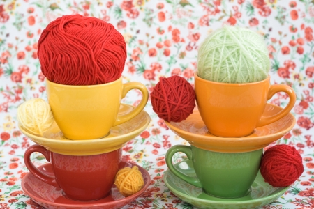 hobie: Four colorful cups and balls of yarn on a background of a red flower