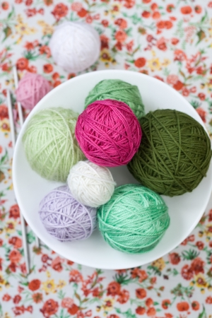 A lot of bright balls of knitting on the background of a red flower photo