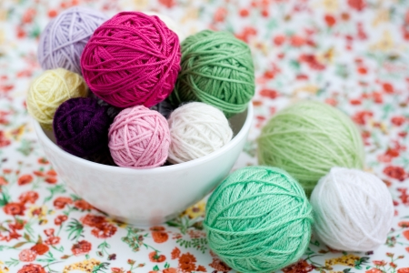 hobie: A lot of bright balls of knitting on the background of a red flower Stock Photo