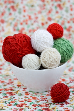 A lot of bright balls of knitting on the background of a red flower Stock Photo - 20923007