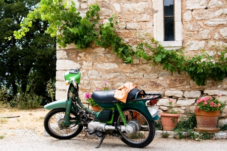 Green Motorcycles stands near the wall of the house photo