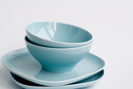 heaped:  Four pale blue plates are heaped on a light background