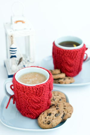 Two blue cups in knitted covers and chocolate cookies photo