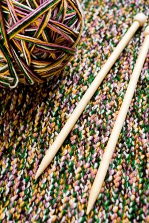 Great ball of colored yarn, wooden knitting needles and knit fabric  photo