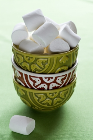 Bright bowls on a green background and white marshmallows photo