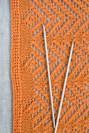 hobie: Openwork pattern with orange thread and a pair needles