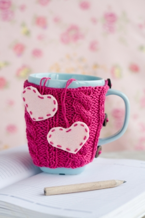 Blue cup in pink sweater with felt hearts standing on an open notebook photo