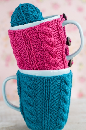 Two blue cups in blue and pink sweater with ball of yarn for knitting photo