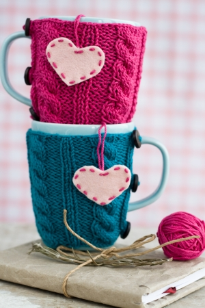 Two blue cups in blue and pink sweater with felt hearts on an notebook  photo
