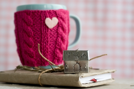 close knit: Blue cup in a pink sweater standing on an old notebook Stock Photo