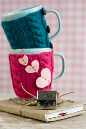 close knit: Two blue cups in pink and blue sweater on an old notebook