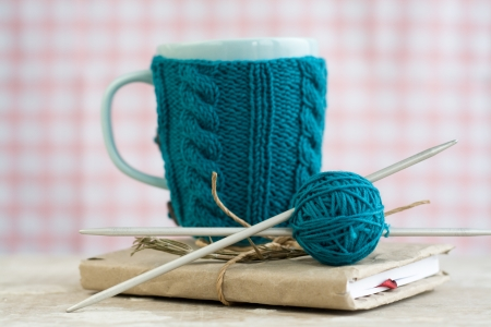 Blue cup in a blue sweater standing on an old notebook Stok Fotoğraf