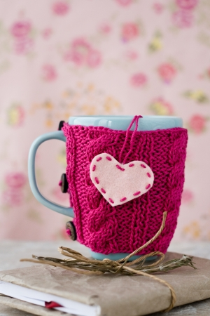 Blue cup in a pink sweater standing on an old notebook Stok Fotoğraf