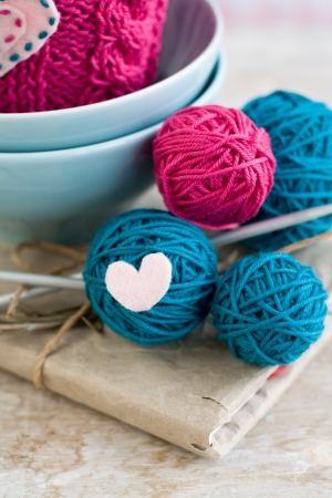 Bright balls of yarn in blue plates and heart made   8203;  8203;of felt photo