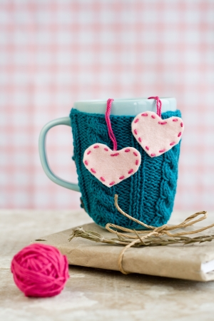 Blue cup in a blue sweater with felt hearts Stok Fotoğraf