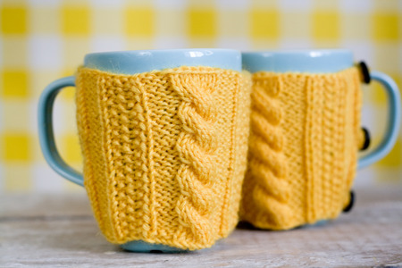 Two blue cups in yellow sweater on a fabric  Stok Fotoğraf