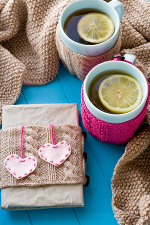 needless: Two blue cup of tea in knitted sweater with hearts felt standing next to the old notebook and blanket knitted on blue background