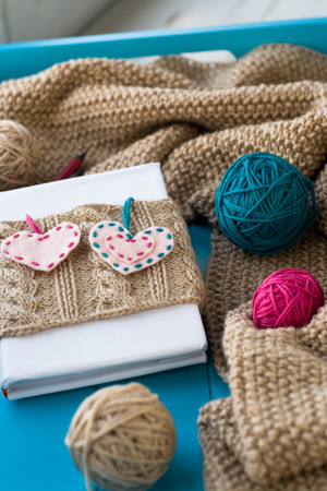 needless: Old notebook with knitted cover with felt heart next to the tangle bright filaments and blanket knitted on blue background
