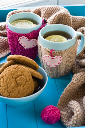 needless: Two blue cup of tea in knitted sweater with hearts felt standing next to tangle bright filaments and blanket knitted on blue background