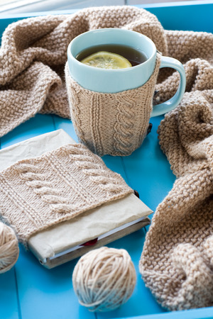 needless: A cup of tea with lemon in sweater,  old notebook, beige knitted blanket and spokes lie on blue background