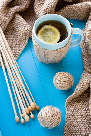 needless: A cup of tea with lemon, beige knitted blanket and spokes lie on blue tray