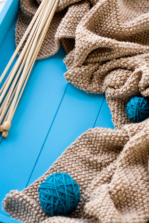 needless: Wooden needles lie next to the bright tangle of threads and knitted blanket on blue background Stock Photo