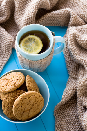 needless: A cup of tea with lemon, biscuits, beige knitted blanket lie on blue tray