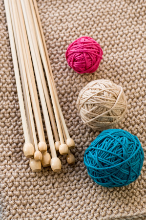 needless: Three colorful balls and wooden needles lying on beige knitted plaid Stock Photo