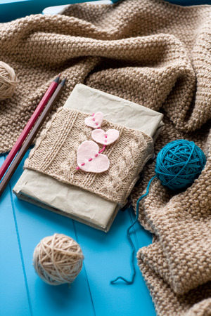 needless: One old notebook in knitted cover with felt hearts lie next to the coil bright filaments and blanket knitted on blue background