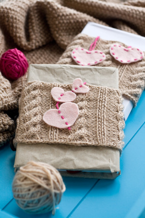 needless: Two old pads in knitted cover with felt hearts lie next to the coil bright filaments and blanket knitted on blue background Stock Photo