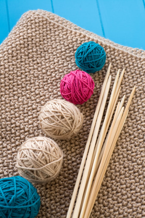 needless: Colorful balls and wooden needles lying on beige