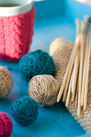 needless: Bright balls of yarn, wooden knitting needles, knitted blanket lying on a blue background