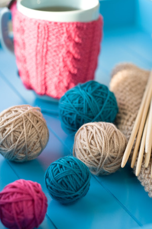 Bright balls of yarn, wooden knitting needles, knitted blanket lying on a blue background photo