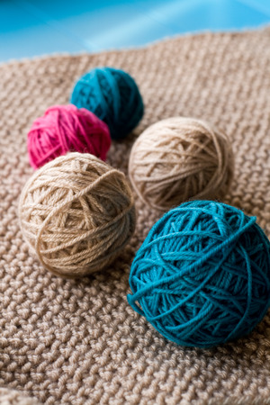 needless: Bright balls of yarn lying on beige knitted plaid