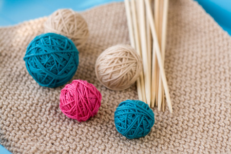 Colorful balls and wooden needles lying on beige photo