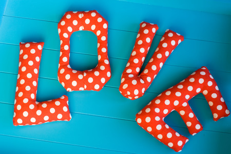 polka dot fabric: The letters with red polka dot fabric LOVE on blue wooden background