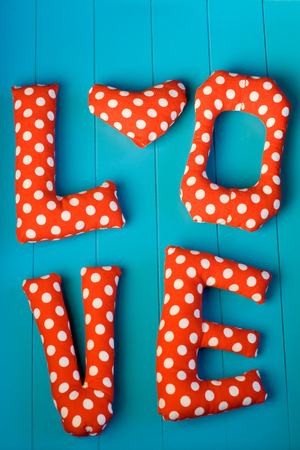 polka dot fabric: The letters with red polka dot fabric LOVE and heart on blue wooden background