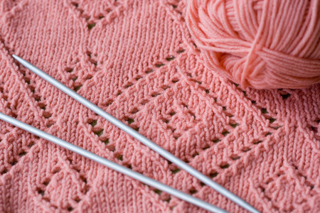 skein: Knitted element pink skein of yarn and knitting needles Stock Photo