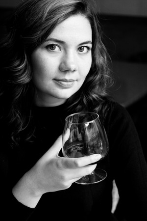 liquor girl: Beautiful young curly brunette holding a glass with alcohol Stock Photo