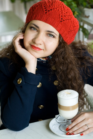 Young beautiful brunette with a delicious latte in a street cafe photo