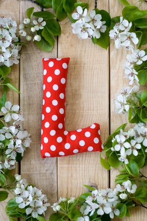l natural: Natural wooden background with white flowers fruit tree. In the middle is the letter L is made of red polka dot fabric. Stock Photo