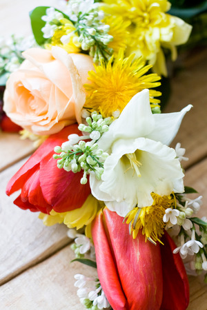 Bouquet of colorful spring flowers lying on the unpainted wooden background photo