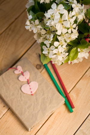 unpainted: A bouquet of white spring flowers and old vintage notebook with bookmark in the form of hearts and pencils lying on the unpainted wooden background Stock Photo