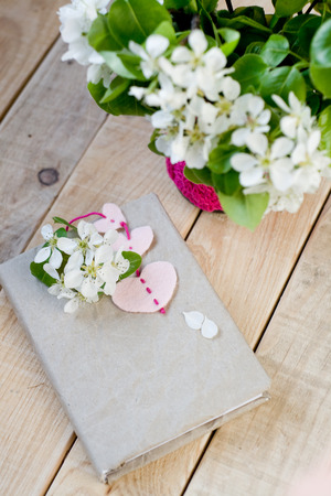 unpainted: A bouquet of white spring flowers and old vintage notebook with bookmark in the form of hearts which lie on the unpainted wooden background