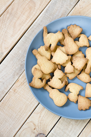 unpainted: Grey plate with tasty cookies in the form of figurines of cats and guitars on unpainted wooden background
