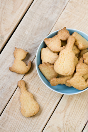 unpainted: Blue plate with tasty cookies in the form of figurines of cats and guitars on the unpainted wooden background