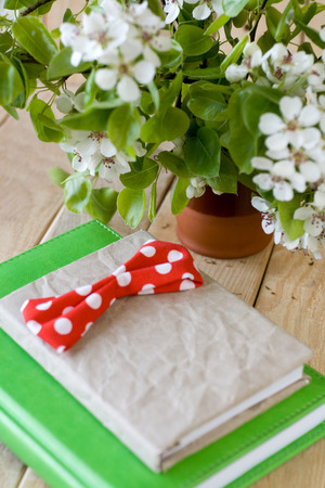 A bouquet of flowering branches of fruit trees and an old notepad on unpainted wooden background photo