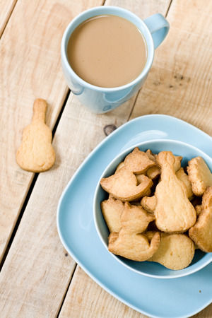 unpainted: Sweet tasty cookies in the blue plate, a cup of coffee with milk and notebook on wooden unpainted background. Stock Photo