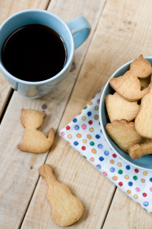 unpainted: Sweet tasty cookies in the blue plate and cup of black coffee on the wooden unpainted background.